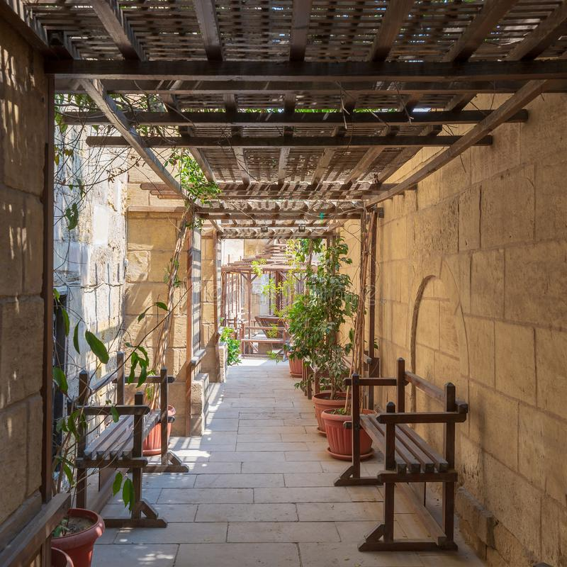Passage ceiled with wooden pergola leading to the historical House of Egyptian Architecture from the Mamluk era, Cairo, Egypt. Passage ceiled with wooden pergola stock photography
