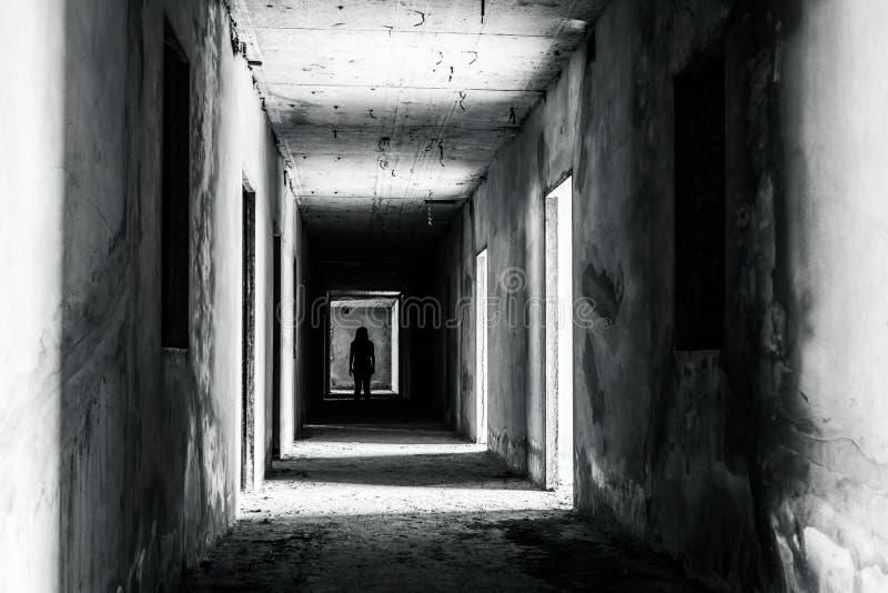 Passage couvert dans le bâtiment abandonné avec la femme effrayante à l'intérieur photo libre de droits