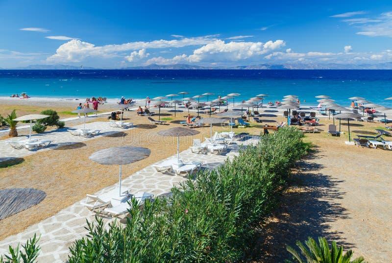 Passage couvert en bois blanc sur la plage comprenant des parapluies avec des chaises de plate-forme Mer Égée La Grèce Rhodes Cai images stock