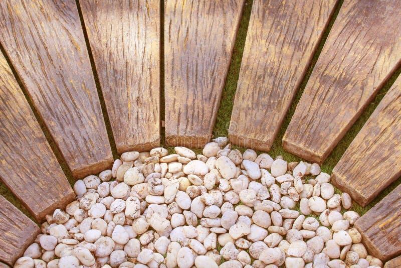 Passage couvert en bois de Brown avec le petit modèle blanc de roches dans le jardin, fond naturel photos libres de droits