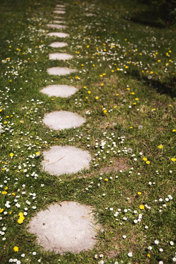 Passage couvert en pierre Passage couvert de chemin de jardin sur le gazon d'herbe verte photo stock