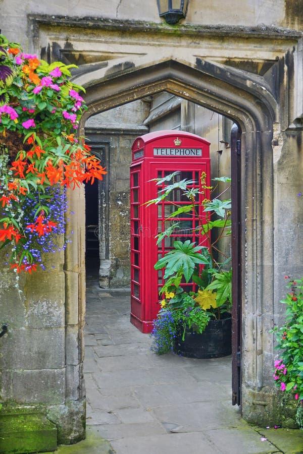 Passage couvert par la porte arquée, fleurs, cabine de téléphone, à l'intérieur de Magdalen College, Oxford images stock