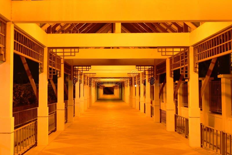 Passage couvert sur le bâtiment avec l'ampoule jaune dans la nuit images libres de droits