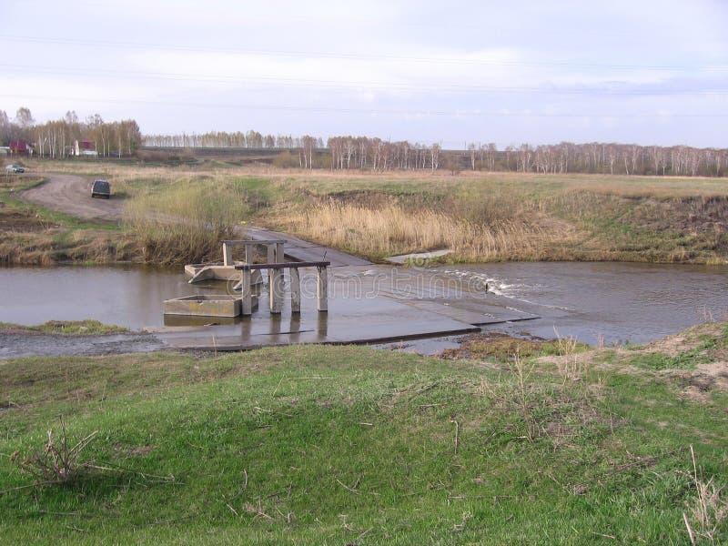 Passage dangereux de route en crue par la rivière dans une inondation sur la catastrophe naturelle détruite de pont en Sibérie photos stock