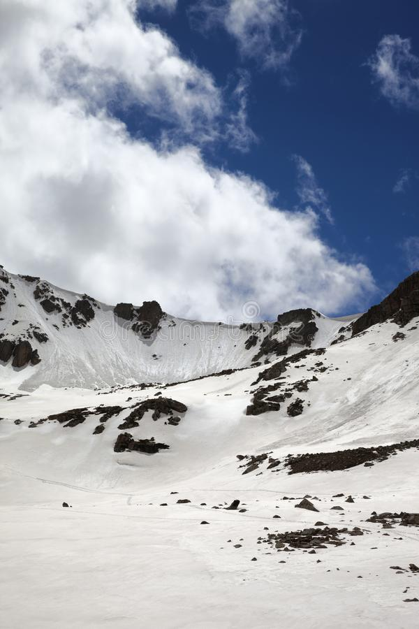 Passage de montagne ensoleillé avec la corniche de neige et le ciel nuageux bleu photos libres de droits
