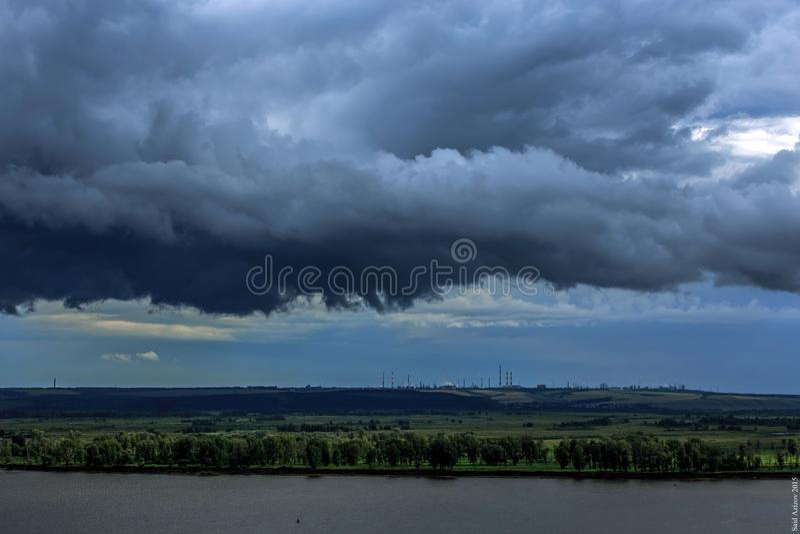 Passage de nuages noirs au-dessus de la rivière image stock