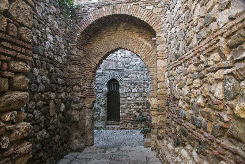 Passage en pierre caché dans la forteresse de Malaga avec les archs et la porte image libre de droits