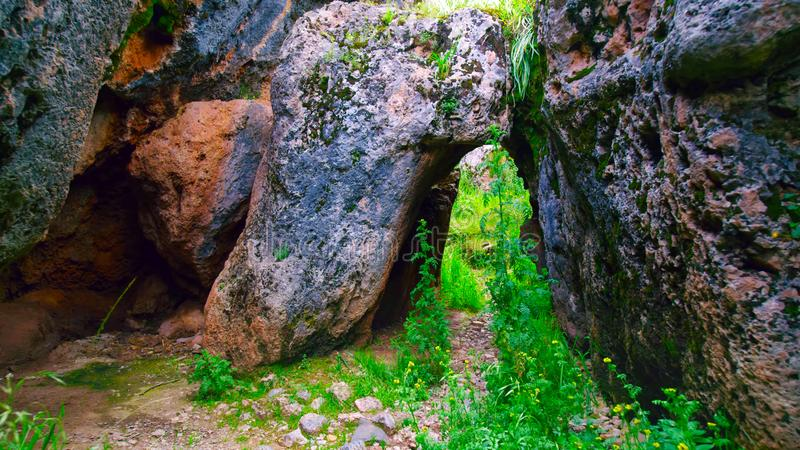 Passage between huge stones in Peru. A passage with green grass between huge stones in Peru stock image