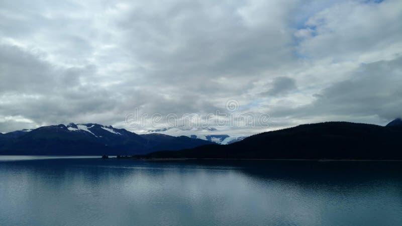 Passage i Stilla havet mellan två bergskedjor Lugna fridsamt vatten som långsamt flödar under en molnig himmel royaltyfri foto