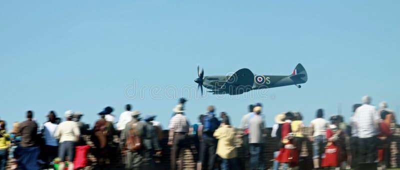Passage inférieur de Spitfire au-dessus de foule photographie stock