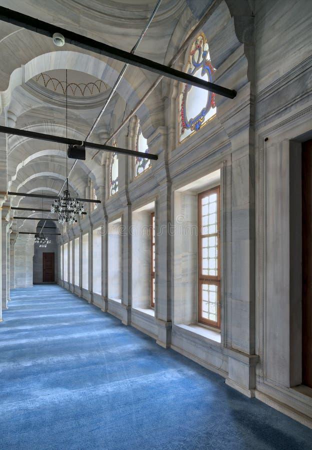 Passage in Nuruosmaniye-Moskee met kolommen, bogen en vloer met blauw die tapijt worden door zijruiten, Istanboel, Turkije wordt  stock foto