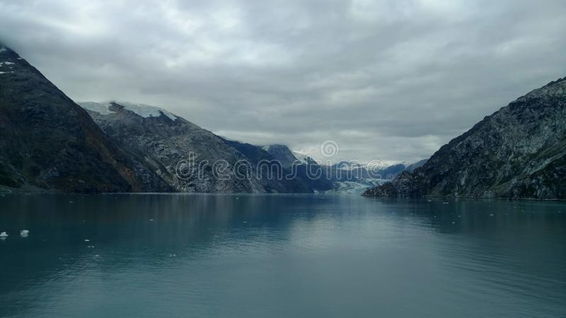 Passage in the Pacific Ocean between two mountain ranges. Calm peaceful waters flowing slowly under a cloudy sky. Glaciers visible at the end of the passage stock photos