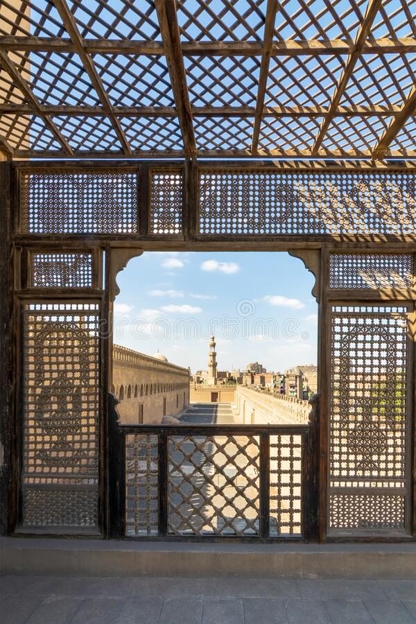 Passage surrounding Ibn Tulun Mosque framed by wooden perforated wall - Mashrabiya - Cairo, Egypt. Passage surrounding the Mosque of Ibn Tulun framed by royalty free stock images