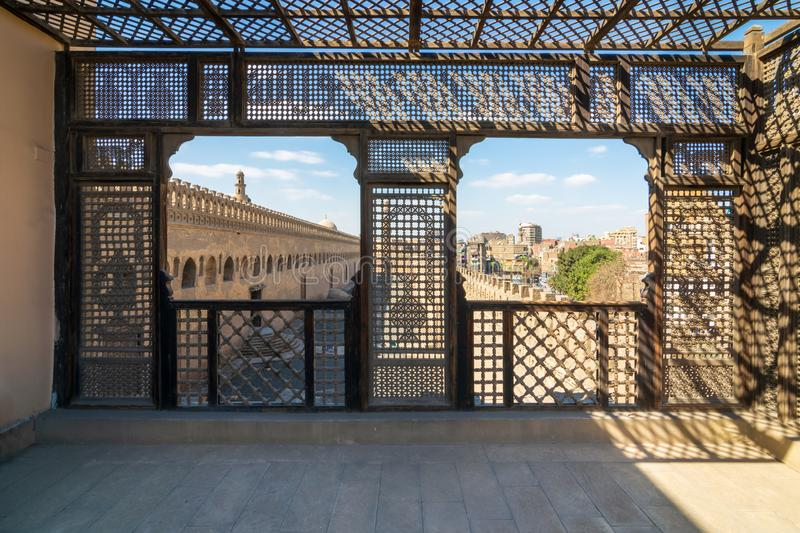 Passage surrounding the Mosque of Ibn Tulun framed by wooden window, Mashrabiya, Cairo, Egypt. Passage surrounding the Mosque of Ibn Tulun framed by interleaved royalty free stock image