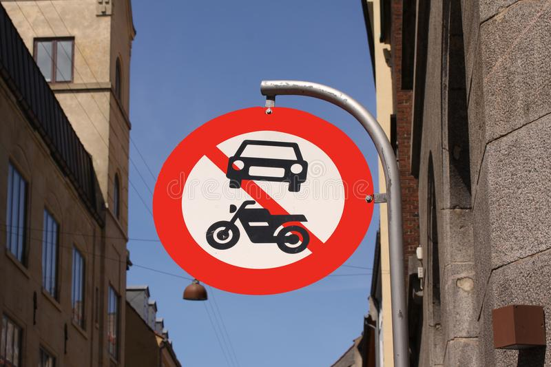The passage of vehicles and motorcycles is prohibited. Round red and white traffic sign in a city with blue sky. Background stock photo