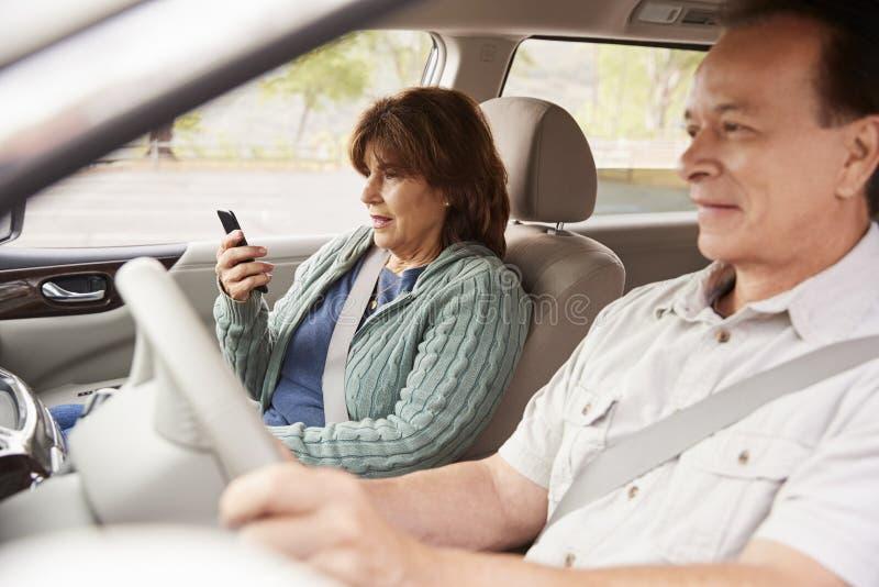Passageiro da mulher que usa GPS no smartphone durante a viagem do carro fotografia de stock royalty free