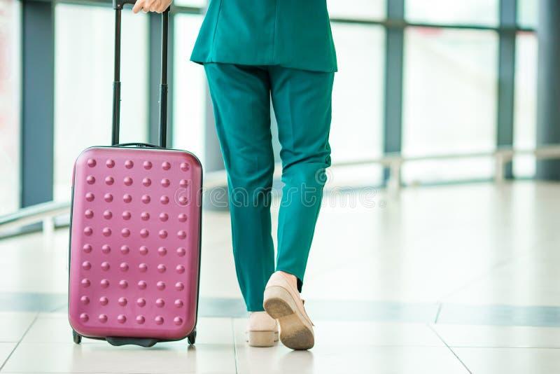 Passageiro do avião dos pés do close up e bagagem cor-de-rosa em uma sala de estar do aeroporto que vai para aviões do voo Jovem  imagem de stock royalty free
