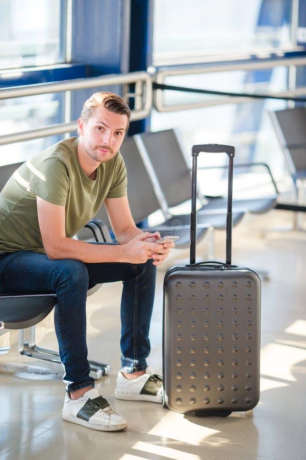 Passageiro em um avião de espera do voo da sala de estar do aeroporto Homem novo com o telefone celular na aterrissagem de espera fotografia de stock