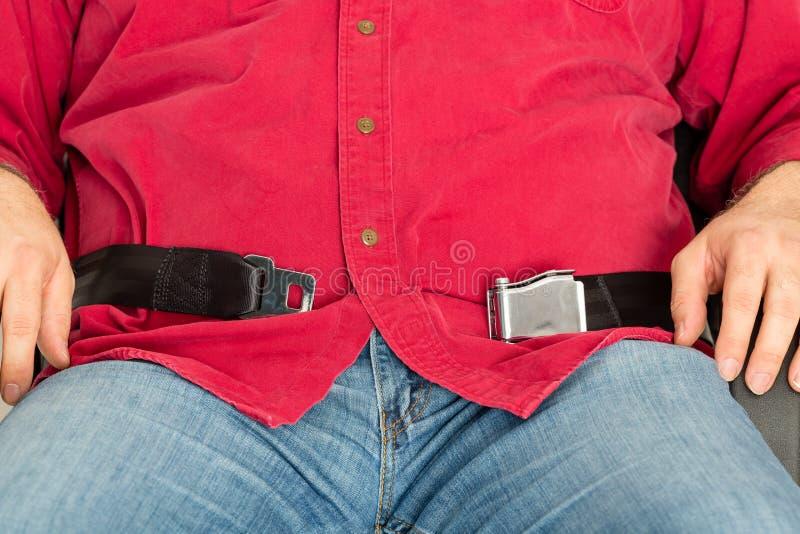 Passageiro obeso incapaz de prender o seatbelt foto de stock royalty free