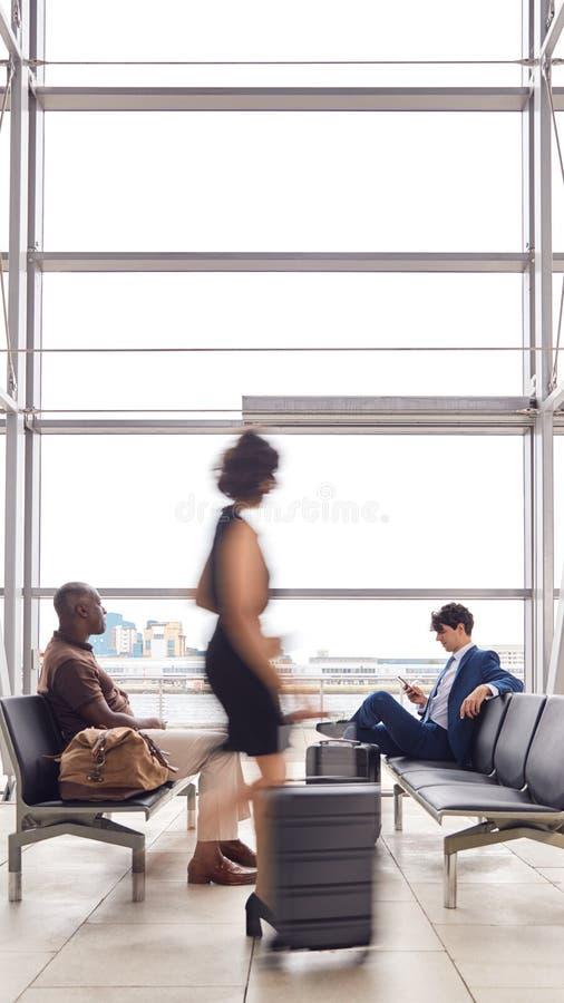 Passageiros De Negócios Sentados Na Sala De Partida Do Aeroporto Ocupado Utilizando Telefones Móveis fotografia de stock royalty free