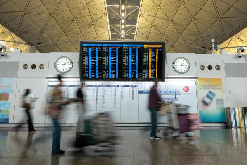 Passageiros e turistas que verificam a programação que voa para dentro do aeroporto de Hong Kong fotografia de stock royalty free