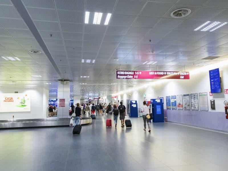Passageiros que andam na reivindicação de bagagem do aeroporto de Milan Bergamo em Bergamo, Itália fotos de stock royalty free