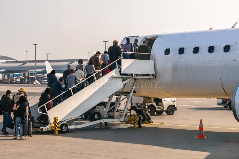 Passageiros que carregam no plano no aeroporto fotos de stock royalty free