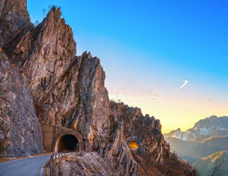 Passagem da estrada da montanha de Alpi Apuane e opinião dobro do túnel no por do sol imagens de stock
