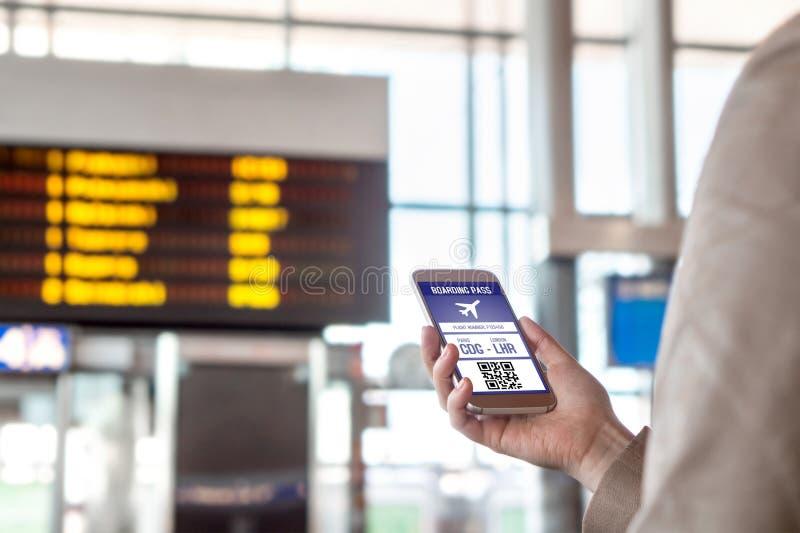 Passagem de embarque no smartphone Mulher que guarda o telefone no aeroporto com o bilhete móvel na tela imagens de stock
