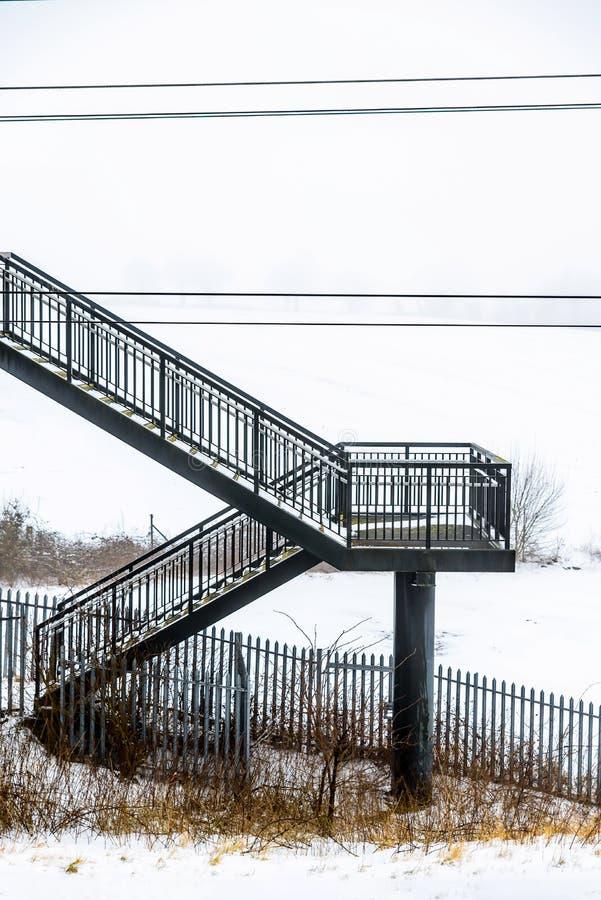 Passagem elevado da ponte pedestre vazia do metal sobre a estrada de ferro britânica fotografia de stock royalty free
