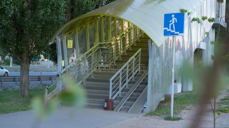 A passagem superior pedestre é equipada com uma rampa moderna para deficientes motores elementos dos trilhos do ferro e vidro col fotografia de stock