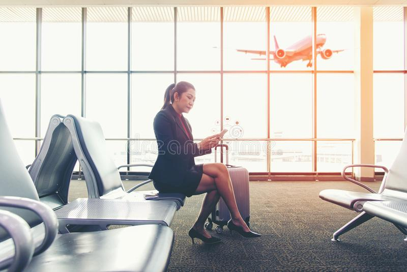 Passager asiatique de femmes d'affaires employant le mobile photos stock