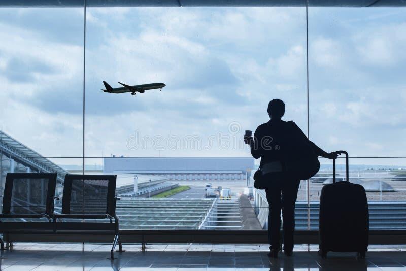 Passager dans l'aéroport regardant le décollage d'avions images stock