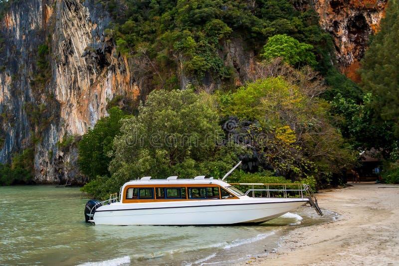 Passager de attente de hors-bord de luxe blanc de moteur sur le rivage d'une île tropicale Amarré sur une plage sablonneuse, de images stock