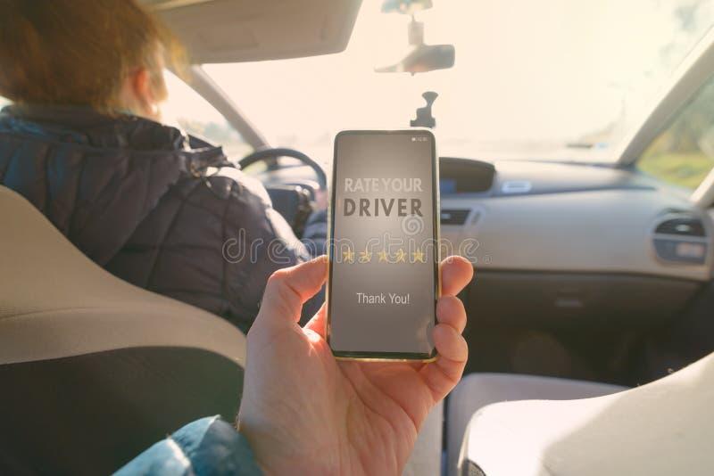 Passager utilisant l'appli futé de téléphone pour évaluer un taxi ou un pair moderne pour scruter conducteur ridesharing photographie stock libre de droits
