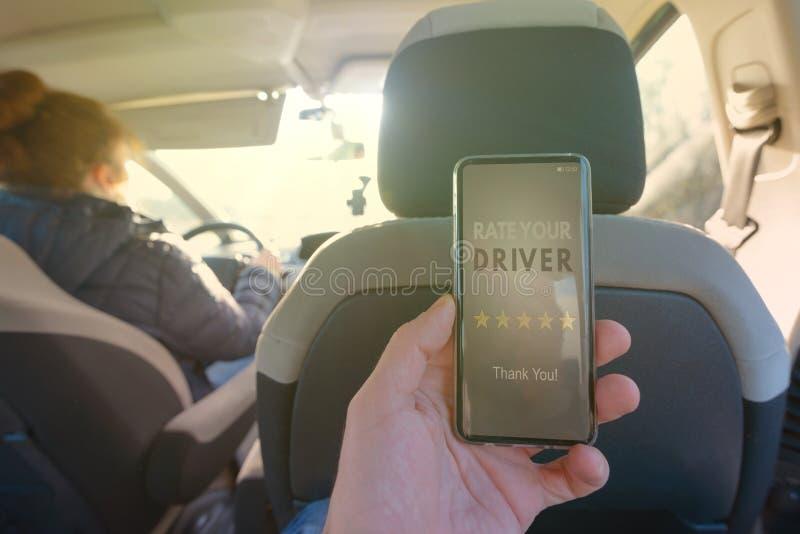 Passager utilisant l'appli futé de téléphone pour évaluer un taxi ou un pair moderne pour scruter conducteur ridesharing photographie stock