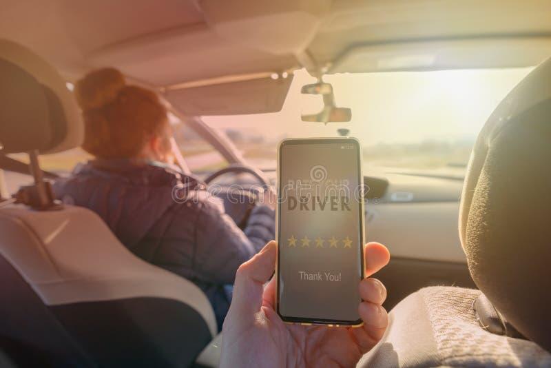 Passager utilisant l'appli futé de téléphone pour évaluer un taxi ou un pair moderne pour scruter conducteur ridesharing image stock