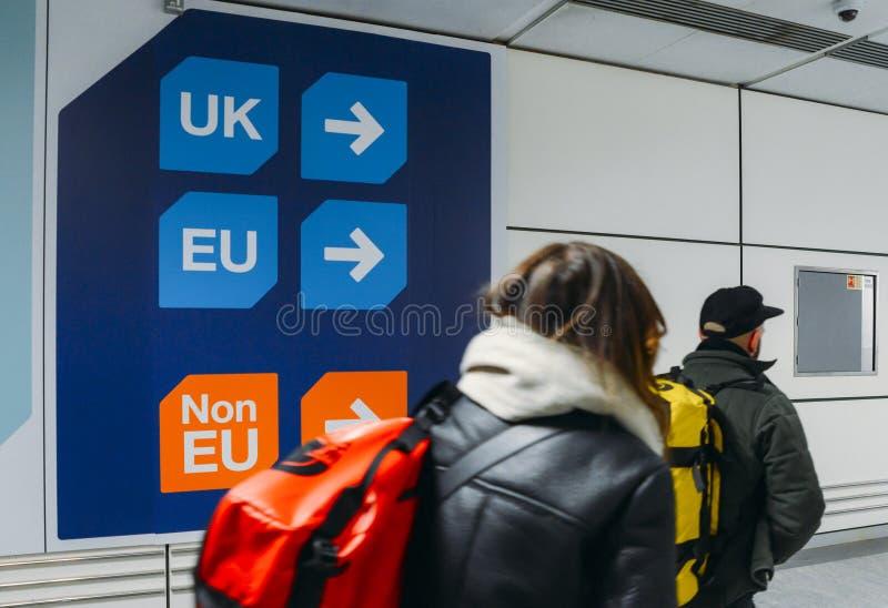 Passagerare går förbi tecken före invandringkontrollpasserande en si arkivfoto
