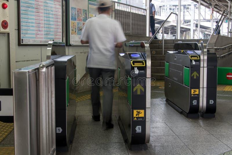 Passagerare går till och med en turniket till plattformen arkivbild