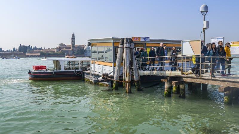 Passagerare landsätter på vattenhållplatsen på Colonna i den Murano ön, Venedig, Italien royaltyfria bilder