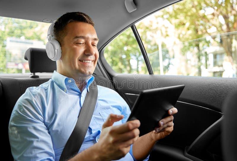 Passagerare med hörlurar med Tablet PC i bil royaltyfri foto
