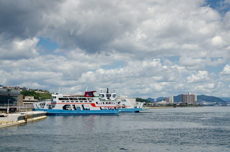 Passagerare och bilf?rja f?r att korsa det inlands- havet mellan den Miyajimaguchi och Miyajima ?n fotografering för bildbyråer