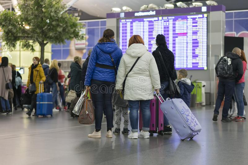 Passagerare på flygplatsen nära informationsbrädet _ royaltyfria bilder