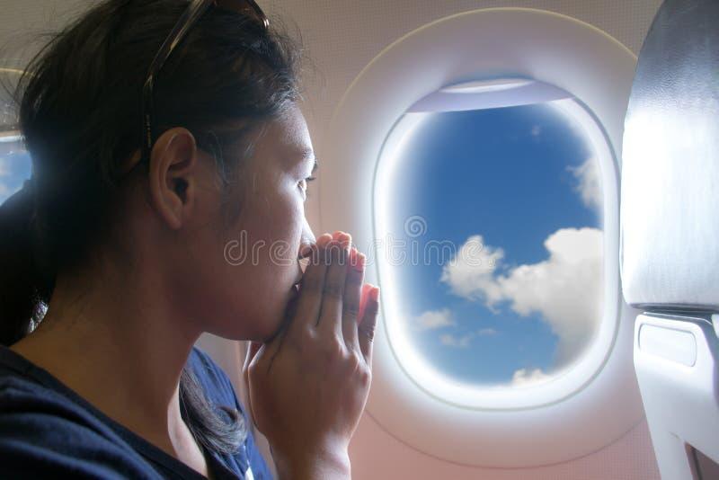 Passagerare som ber i ett flygflygplan royaltyfri bild