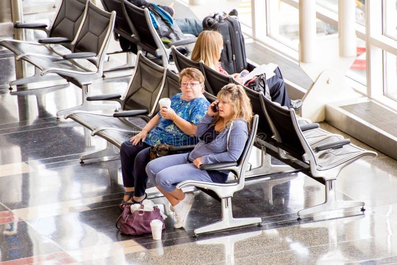 Passagerare som framme väntar av ett ljust inre flygplatsfönster royaltyfri bild