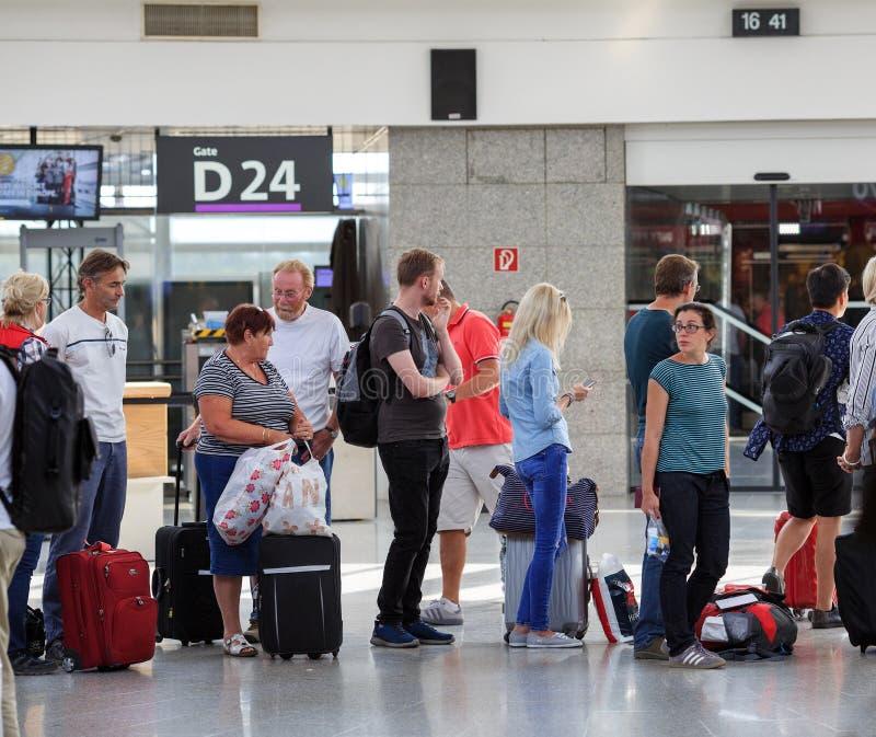Passagerare som står i linje i Wien den internationella flygplatsen Schwechat, Österrike royaltyfria bilder