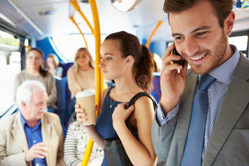 Passagerare som står på den upptagna pendlarebussen royaltyfria bilder