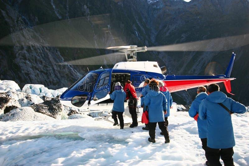 Passagerare som stiger ombord helikoptern som landas på is fotografering för bildbyråer