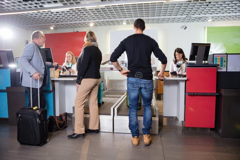 Passagerare som väger deras bagage på flygplatsen arkivbilder