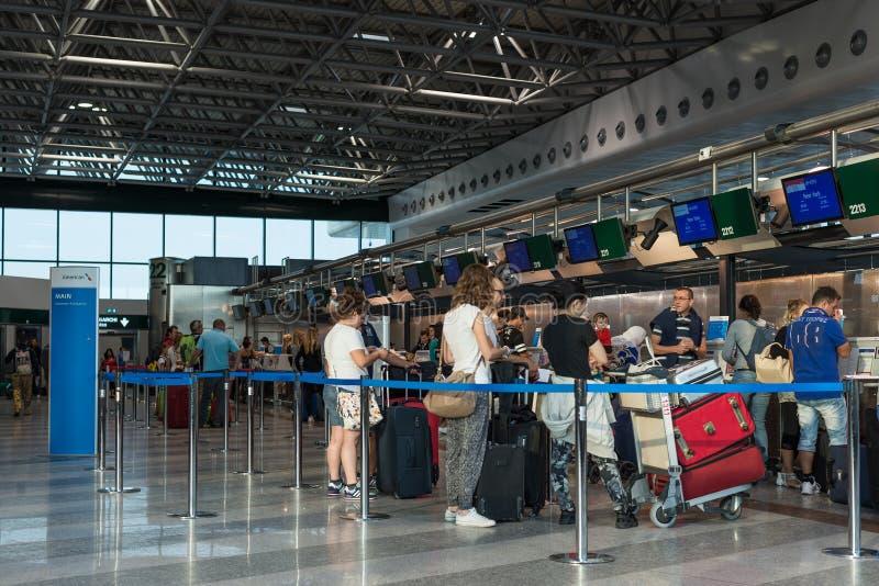 Passagerare som väntar i kö på American Airlines, kontrollerar in räknaren på Malpensa den internationella flygplatsen, Milan, It arkivbilder